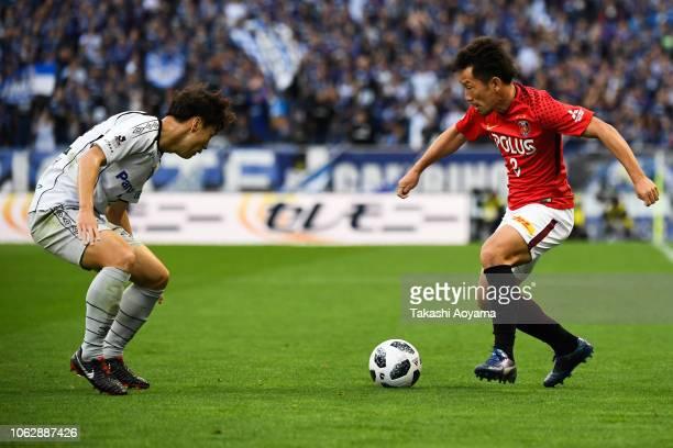 Oh Jae Suk of Gamba Osaka and Tomoya Ugajin of Urawa Red Diamonds compete for the ball during the J.League J1 match between Urawa Red Diamonds and...