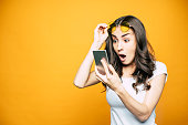 Oh, my! Gorgeous girl with a phone in her hand is surprised by something she saw on the screen is holding her glasses in front of bright yellow background.