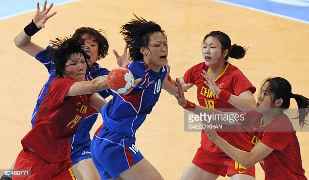 Oh Seongok of South Korea tries to dodge Li Bing Wu Wenjuan and Liu Xiaomei fight for the ball during their 2008 Beijing Olympic Games women's...