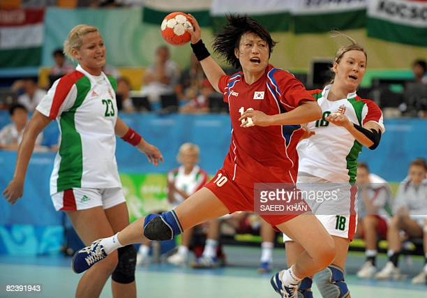 Oh Seongok of South Korean takes a shot for a goal as Piroska Szamoransky and Gabriella Szucs of Hungary defend during their 2008 Beijing Olympic...
