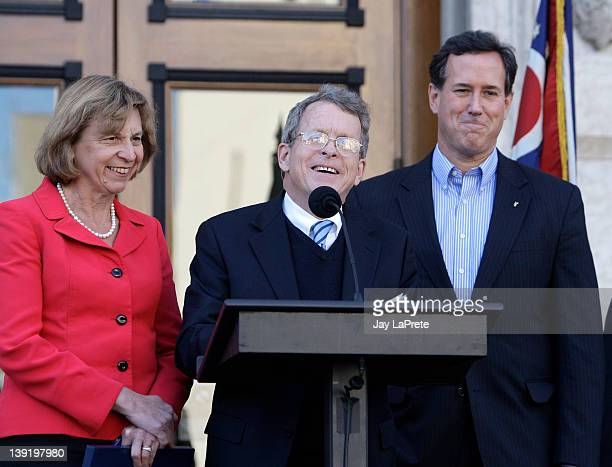 Ohio Attorney General Mike Dewine speaks at a news conference as his wife Fran and Republican presidential candidate former US Sen Rick Santorum look...