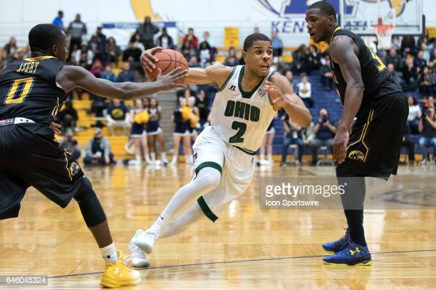 Ohio Bobcats G Jaaron Simmons drives to the basket between Kent State Golden Flashes G Jalen Avery and Kent State Golden Flashes G Deon Edwin during...