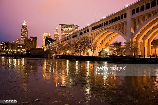 usa, ohio, cleveland, bridge crossing cuyahoga river at dusk - cleveland ohio stock pictures, royalty-free photos & images