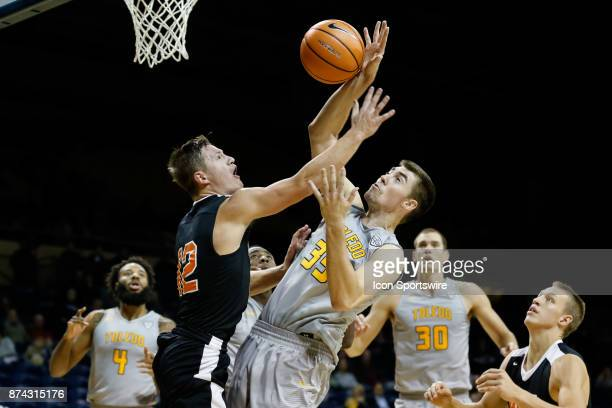 Ohio Northern Polar Bears guard Nate Burger and Toledo Rockets forward Nate Navigato battle to grab a rebound during a regular season game between...