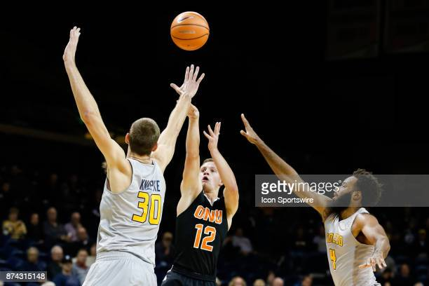 Ohio Northern Polar Bears guard Nate Burger shoots a jump shot over Toledo Rockets forward Luke Knapke and Toledo Rockets guard Tre'Shaun Fletcher...