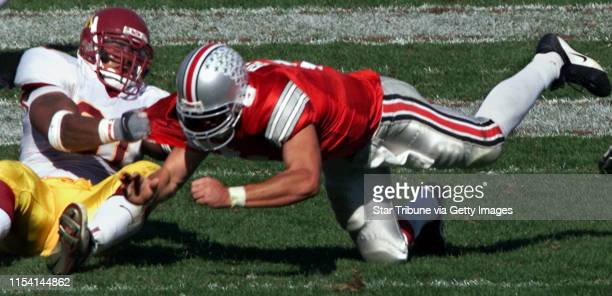 Ohio quarterback Steve Bellisari is thrown to the ground by Gopher defensive end Karon Riley after being rushed into throwing an incomplete pass in...