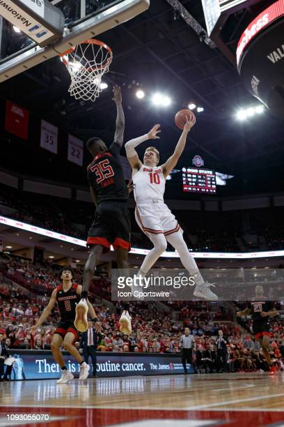 Ohio State Buckeyes forward Justin Ahrens attempts a layup as Rutgers Scarlet Knights forward Issa Thiam defends in a game between the Ohio State...