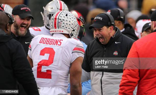 Ohio State Buckeyes Head Football Coach Ryan Day celebrates with J.K. Dobbins during the fourth quarter of the game against the Michigan Wolverines...