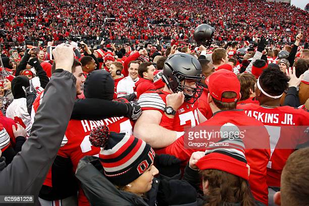 Ohio State Buckeyes players and fans celebrate on the field after their doubleovertime victory over the Michigan Wolverines at Ohio Stadium on...