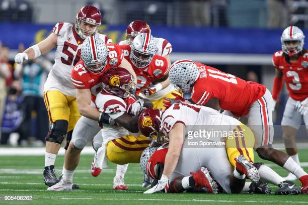 Ohio State Buckeyes players including defensive end Nick Bosa tackle USC Trojans running back Ronald Jones II during the Cotton Bowl Classic matchup...