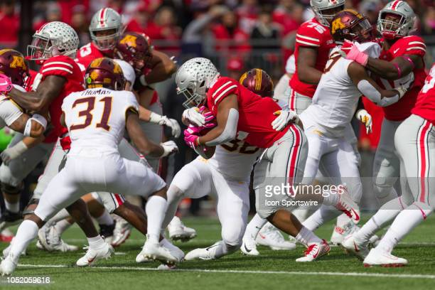 Ohio State Buckeyes running back JK Dobbins fights for a few yards in heavy traffic in a game between the Ohio State Buckeyes and the Minnesota...
