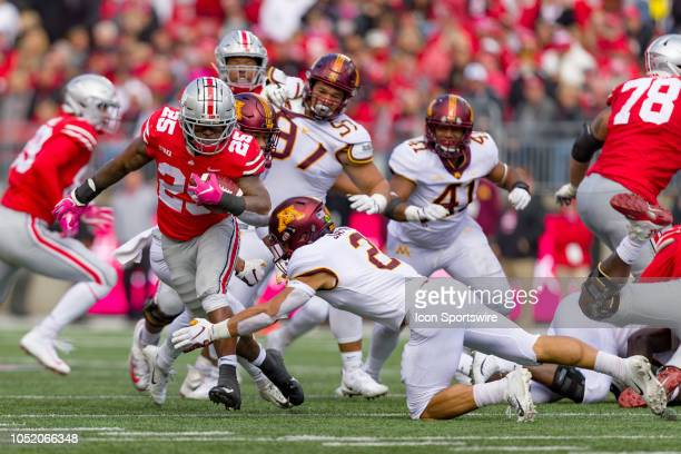Ohio State Buckeyes running back Mike Weber rushes the ball as Minnesota Golden Gophers defensive back Jacob Huff attempts a tackle in a game between...