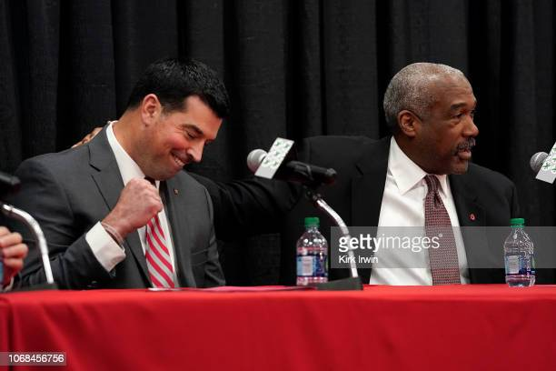 Ohio State University athletics director Gene Smith pats offensive coordinator Ryan Day on the back during a press conference announcing both the...