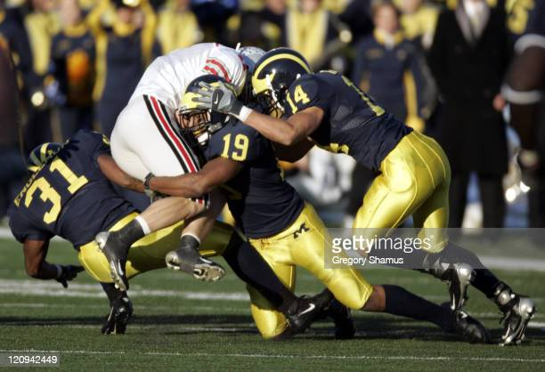 Ohio State University's Anthony Gonzalez takes a hard hit from University of Michigan's Willis Barringer Brandent Englemon and Morgan Trent during...