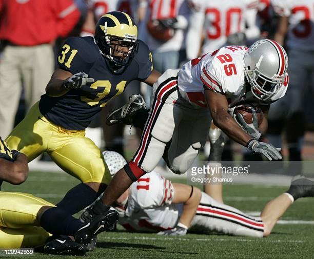Ohio State University's Antonio Pittman tries to find yards with University of Michigan's Brandent Englemon defending at Michigan Stadium in Ann...