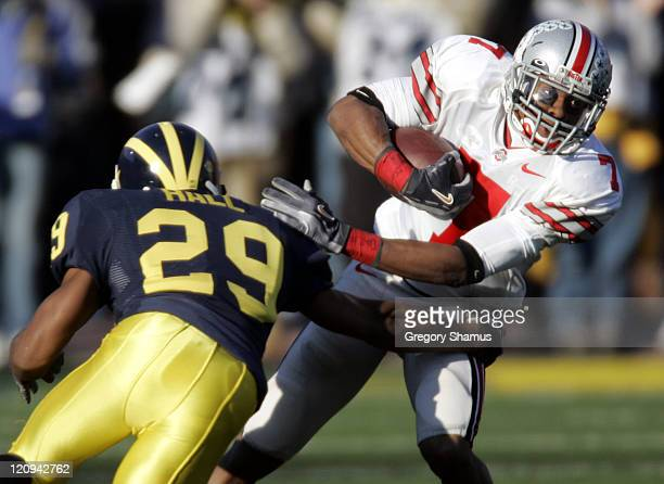 Ohio State University's Ted Ginn Jr #7 tries to escape the tackle of University of Michigan's Leon Hall at Michigan Stadium on November 19 2005 Ohio...