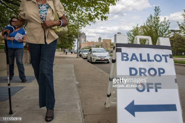 Ohio voters walk to drop off their ballots at the Board of Elections in Dayton, Ohio on April 28, 2020. - On March 17, 2020 Governor Mike DeWine and...