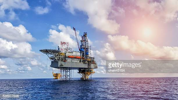 Oil and gas drilling rig working on remote wellhead platform to drill the oil and gas reservoir industry