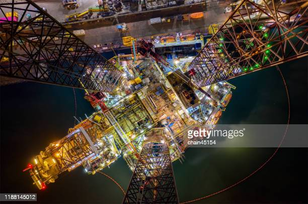 oil and gas jack-up rig at the yard for maintenance with many vessels in the nighttime, the petroleum rig is applied for producing oil and gas in offshore in the petroleum industry. - gas stock pictures, royalty-free photos & images