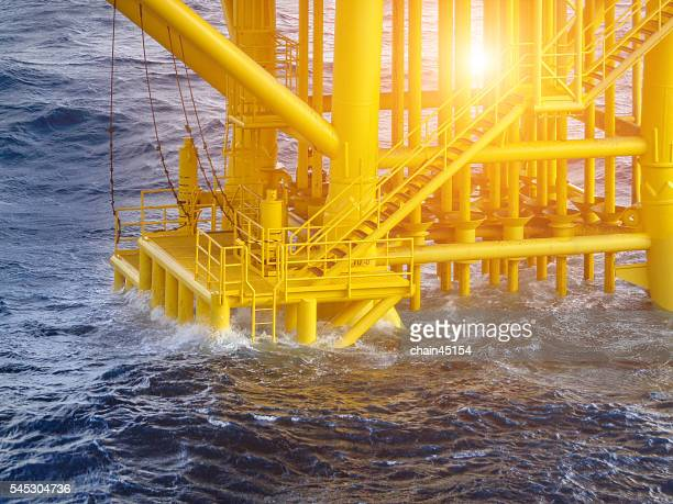 Oil and gas platform with the wave of sea or gulf in the oil and gas industry. Construction for wellhead platform in the world of fuel energy.
