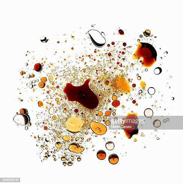 Oil and vinegar droplets on white background