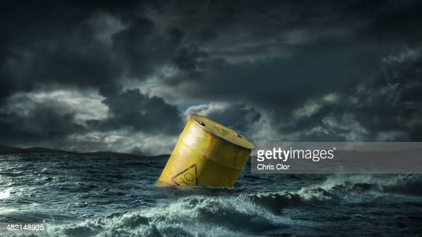 oil barrel floating in stormy sea - drum container stock photos and pictures