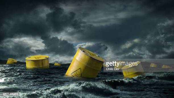 oil barrels floating in stormy sea - drum container stock photos and pictures