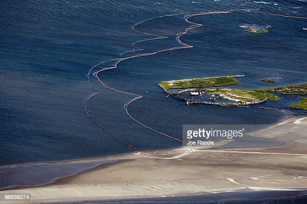 Oil booms are seen surrounding an island as they try to protect it from the massive oil spill on May 9 2010 in Gulf of Mexico The Deepwater Horizon...