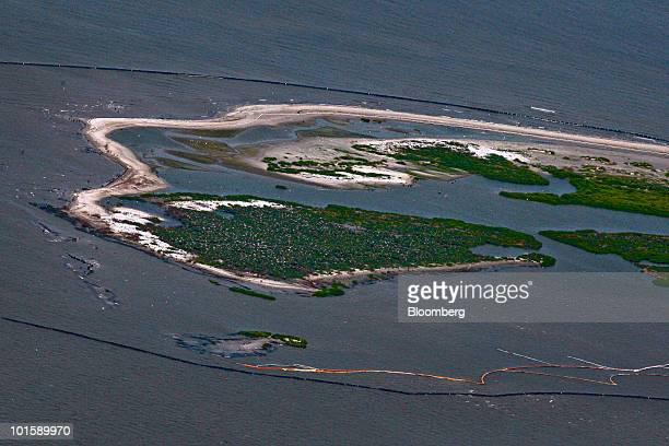 Oil booms circle one of the Chandeleur Islands in Louisiana US which are near the BP Plc Deepwater Horizon oil spill site in the Gulf of Mexico on...