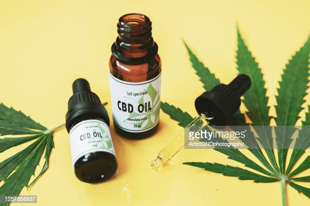 cbd oil, cannabis oil on yellow background. - cbd oil stock pictures, royalty-free photos & images
