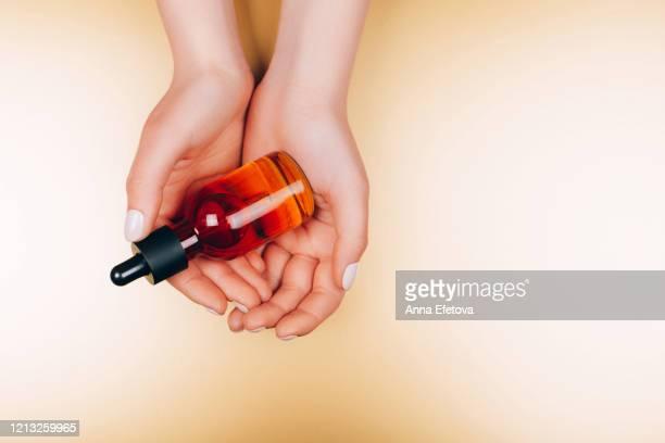 oil care cosmetics in woman's hands - óleo essencial imagens e fotografias de stock