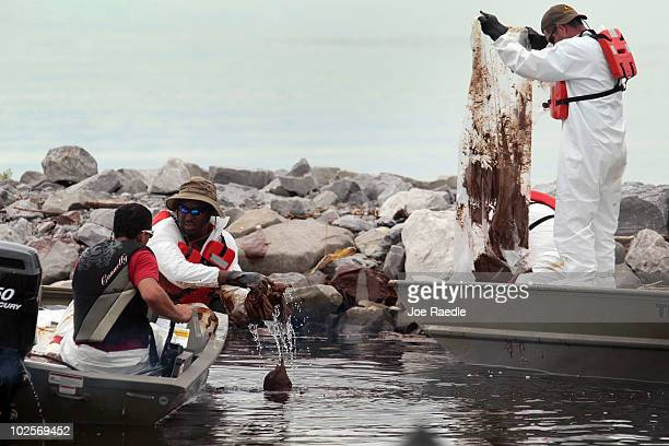 Oil cleanup workers try to remove thick oil that washed ashore from the Deepwater Horizon oil spill in the Gulf of Mexico on July 1 2010 in Gulfport...