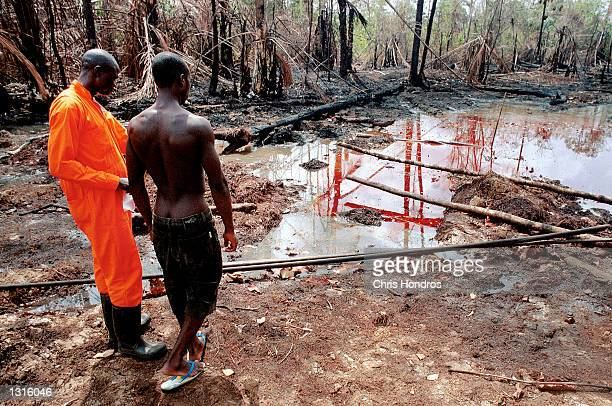 Oil company workers survey an oil spill at the Shellowned Etelebu flow station March 8 2001 in Etelebu Nigeria Nigeria is the world''s sixth leading...