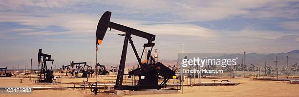 oil drilling field with mountains beyond - timothy hearsum photos et images de collection
