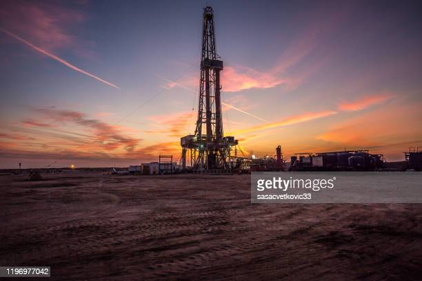 oil drilling platform at sunset - fracking stock pictures, royalty-free photos & images