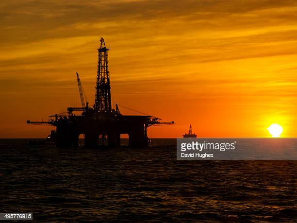 Oil drilling rigs in the Campos Basin oil fields of Brazil with the sun setting.