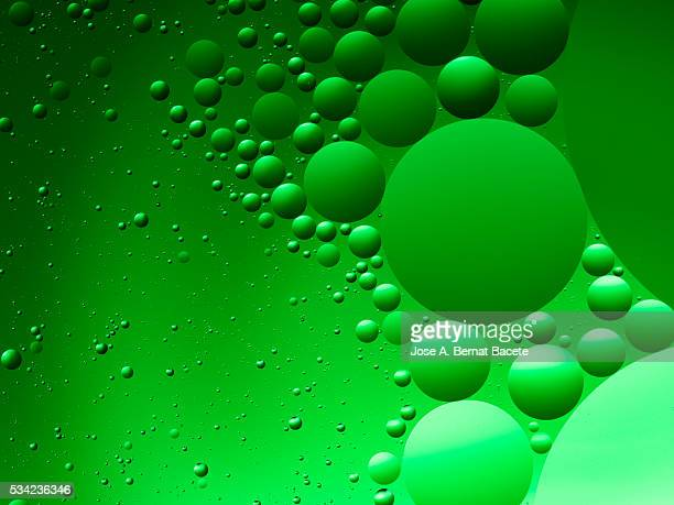 Oil drops and bubbles floating over water with a green background