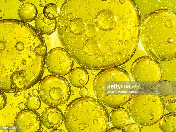 Oil drops and bubbles floating over water with a  yellow background