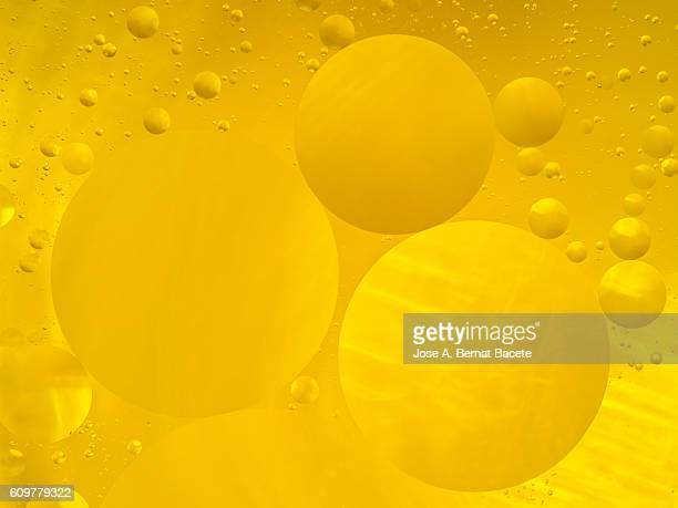 Oil drops and bubbles floating over water with a  yellow colored  background