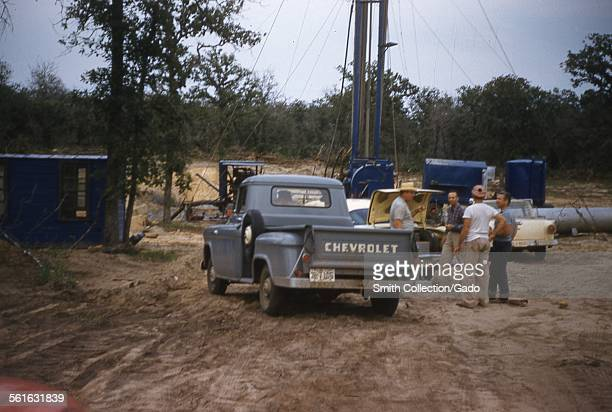 Oil field workers AKA roughnecks with drilling rig truck and Chevrolet pickup truck drilling an oil well Texas 1954