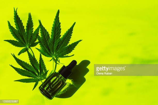 oil in a frosted and transparent glass jars with a pipette and leaves of marijuana - cannabinoid stock pictures, royalty-free photos & images