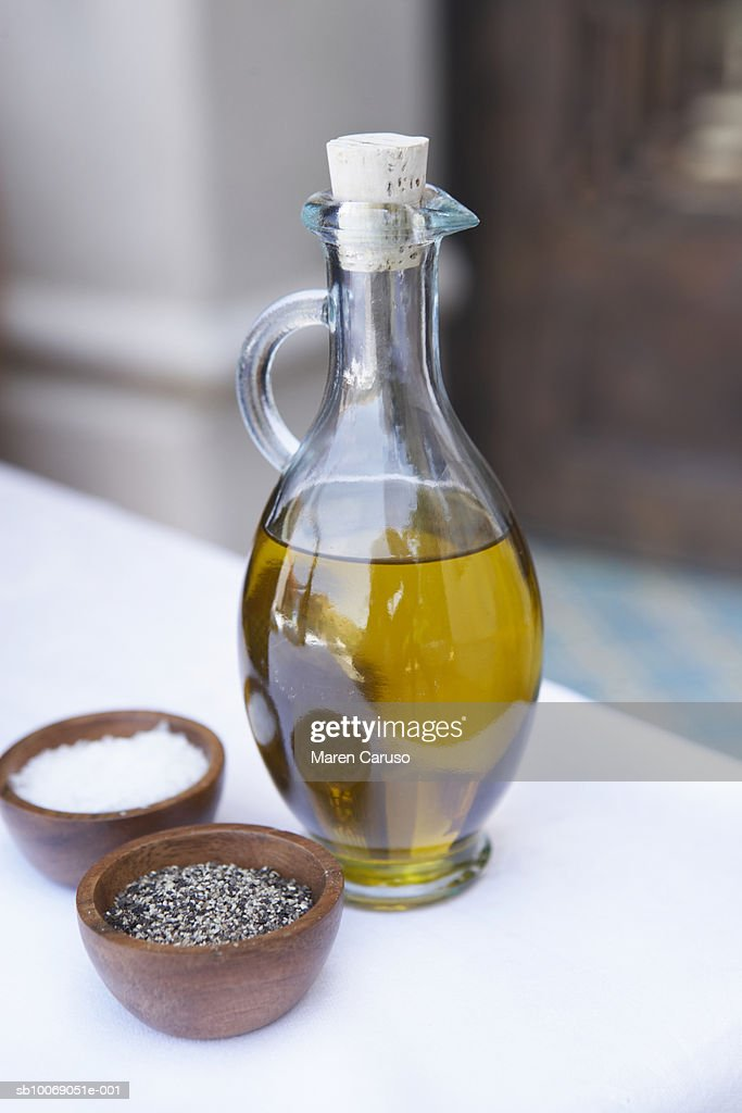 Oil in glass pitcher with bowls of salt and pepper, close-up : Stockfoto