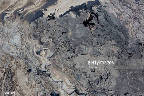Oil is seen at the ground's surface near Royal Dutch Shell Plc's Albian Sands mine near Fort McMurray Alberta Canada on Tuesday Aug 13 2013 Canadian...