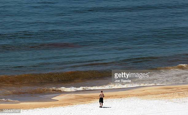 Oil is seen in the water as it washes ashore from the Deepwater Horizon oil spill in the Gulf of Mexico on June 26 2010 in Orange Beach Alabama...