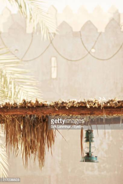 Oil Lamp Hanging From Thatched Roof Against Fortified Wall