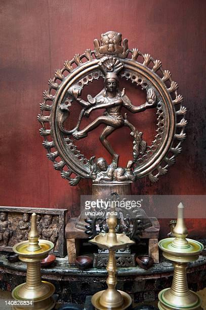 Oil lamps in front of a statue of Nataraj, Kochi, Kerala, India