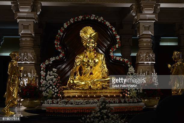 Oil lit lamps are kept in front of an idol of Lord Swaminarayan at the illuminated Akshardham Temple in Gandhinagar some 30 kms from Ahmedabad on the...