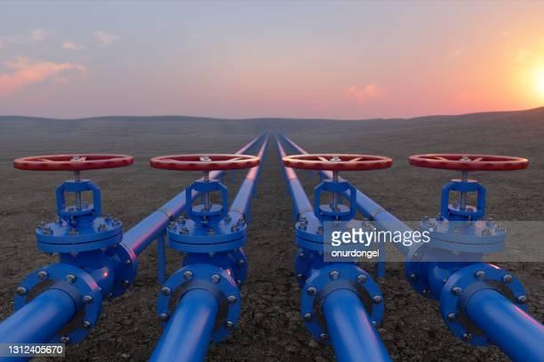 土壌と日の出の背景に青いガスまたは配管バルブを使用した石油またはガス輸送 - ガソリン ストックフォトと画像