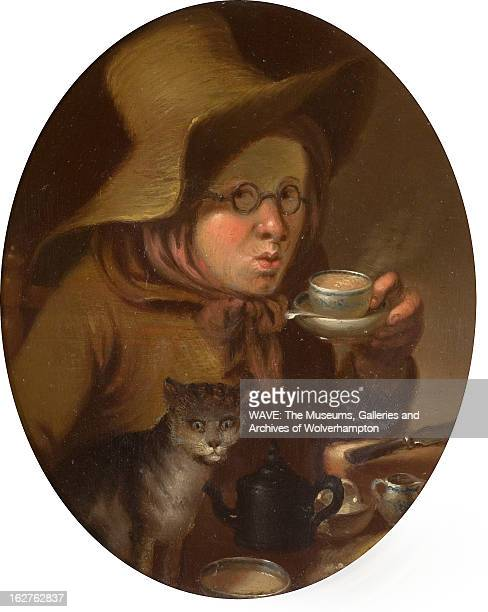 Oil painting portrait of a woman drinking tea She is wearing a large brown hat and a brown jacket and scarf A cat stands beside her England Britain...