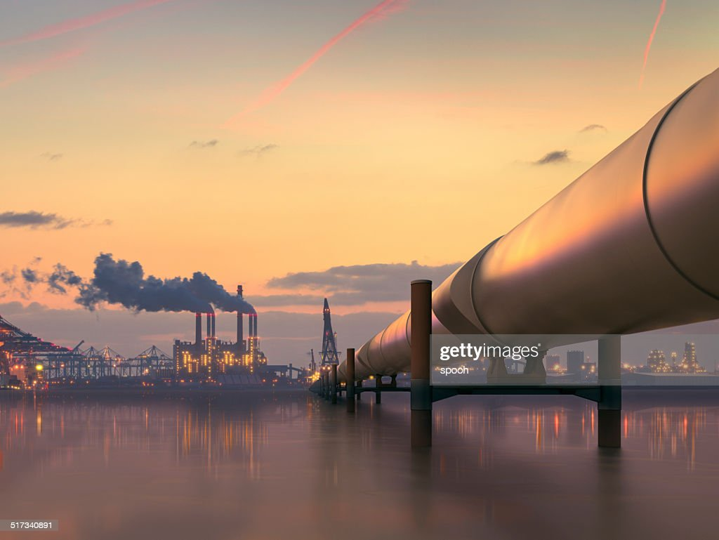 Oil pipeline in industrial district with factories at dusk : Stock Photo